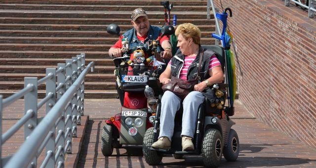 dos personas en scooter eléctrico