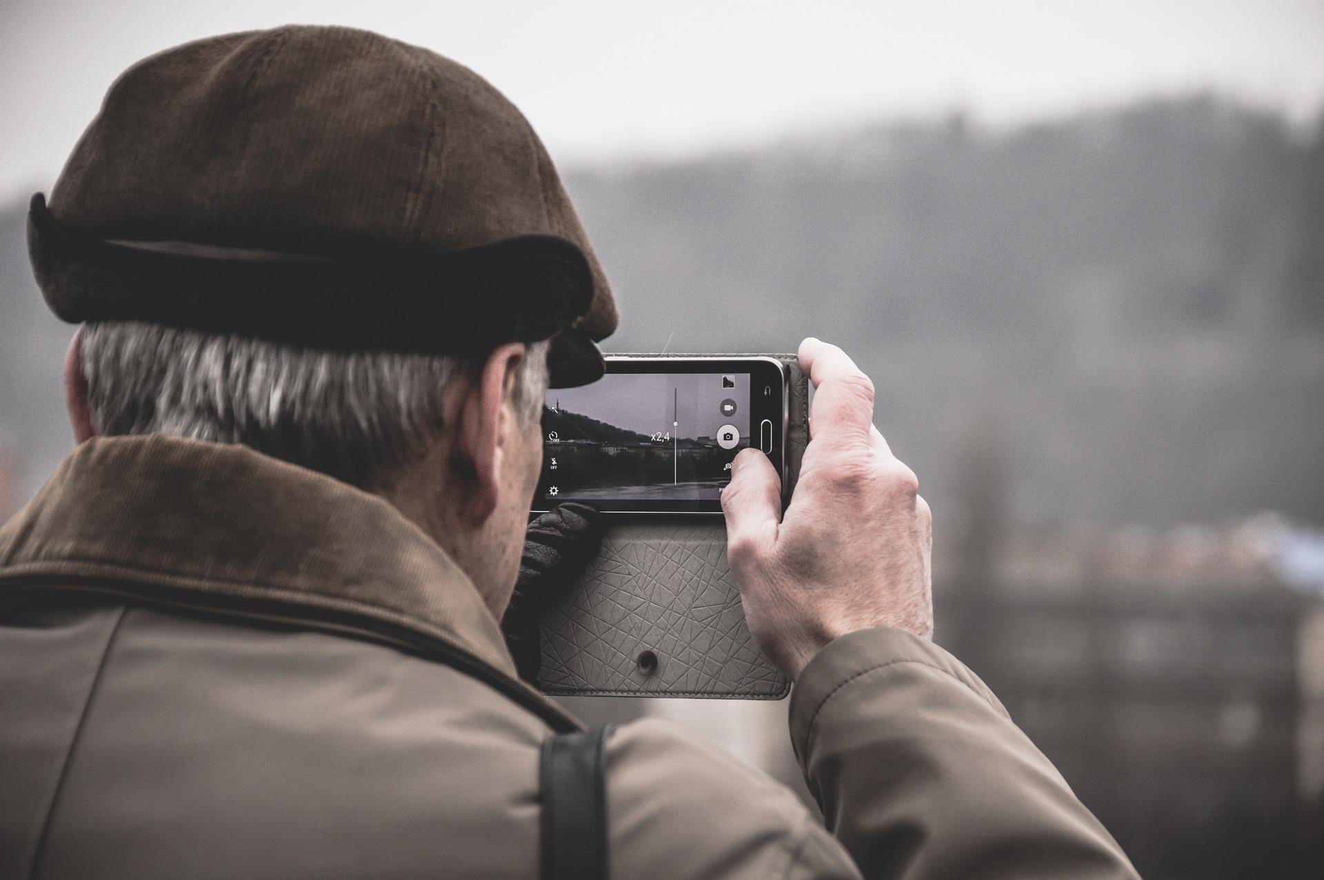 persona mayor haciendo fotografía con smartphone