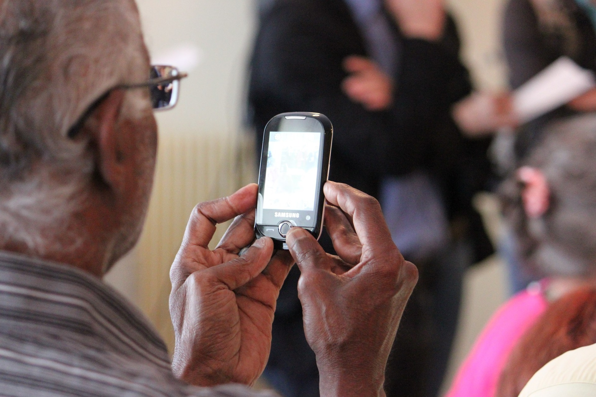 persona mayor usando teléfono móvil