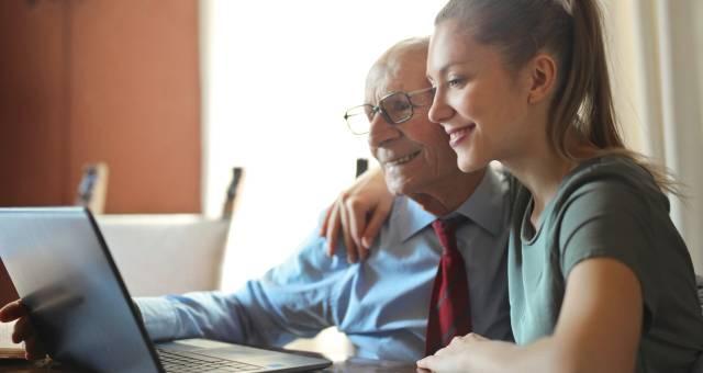 joven y persona mayor de 70 usando laptop